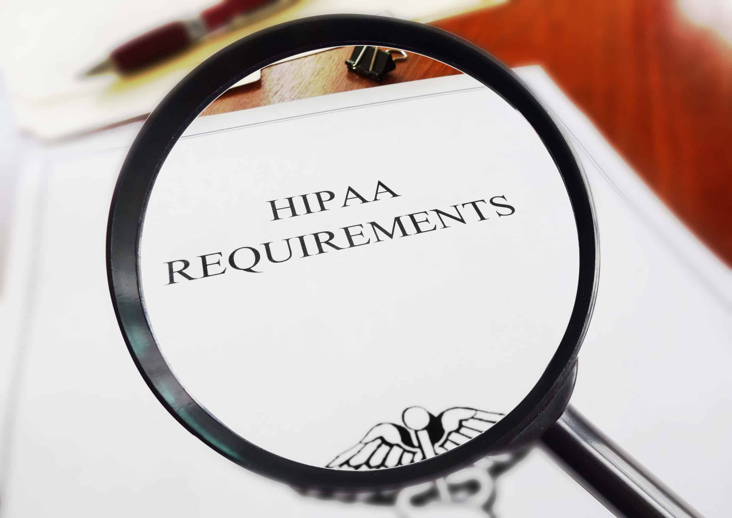HIPAA requirements on a document under a magnifying glass.